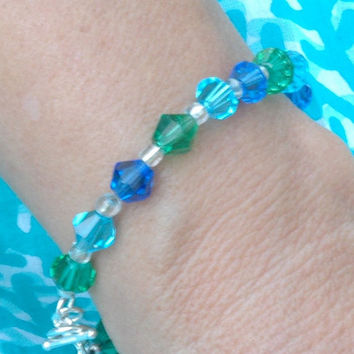 Bracelet with 3 shades of aqua glass beads and silver toggle clasp.