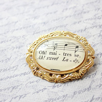 Sheet music brooch.  Romantic French song jewelry made with vintage sheet music in gold pinback setting.