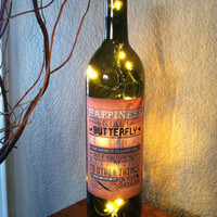 Happiness quote on wine bottle light. Happiness is like a butterfly.. Henry David Thoreau quote.