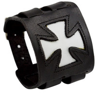 A wide black leather bracelet with a white pattee cross and decorative stitching