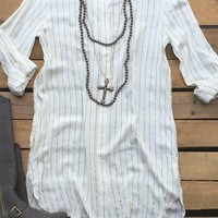 Our Here I Go Again Tunic Top - Ivory is perfect for those chilly nights! It's a long sleeve plaid tunic. Has collar and buttons all the way down the front. Stripe pattern. Chest pocket as well as side pockets.