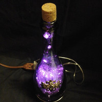The Original Liquor Lights - Segura Viudas Champagne Bottle with Purple LEDs. Heavy metal base with adornment on the side.