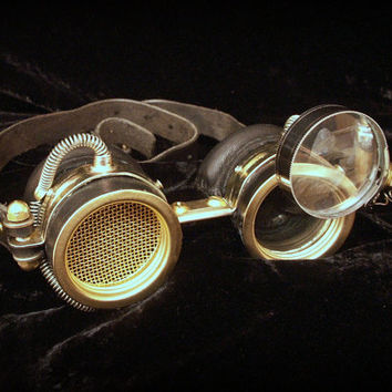 Steampunk goggles in black leather and brass with golden mesh, wrapped wire and moveable loupe.