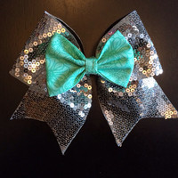 Silver sequin cheer bow with a teal mini in the middle