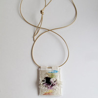 Textile pendant necklace hand embroidered with abstract design on muslin with browns greens lavender peach and yellow on a gold leather cord