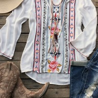 Our Better Be Good To Me Tunic Top is a wide sleeve tunic top with multi color embroidery detail to the front. Keyhole neck with tie closure. Made to be loose fitted. We suggest wearing a cami underneath for coverage.