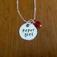 """Paper book inspired """"Paper Girl"""" necklace. Silver colored with a red Swarovski Elements crystal."""
