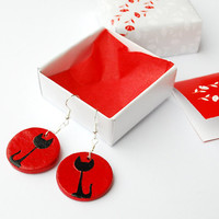Red earrings with black cat silhouette.