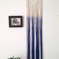 Macrame wall hanging, dip dyed ombre in icy blue, cotton on a wood dowel. Geometric triangle shapes.