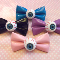 Creepy cute eyeball pvc bow hair clips in black, pink, blue, and purple