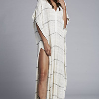 Easy, effortless thin striped pattern knit poncho cardigan featuring a lightweight quadruple-blend fabrication. Semi sheer textured knit, deep v-neckline with half button placket, side splits, short sleeves and a slouchy silhouette. pair with crop top, ski
