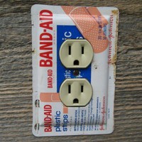 Outlet Cover Made From A Vintage Band Aid Tin For The Bathroom