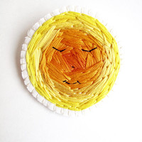 Hand embroidered sun brooch with bright yellow and orange colors on cream muslin with a cream felt backing An Astrid Endeavor Fall fashion
